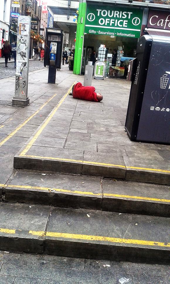 una persona ubriaca addormentata in centro. la scena è ricorrente