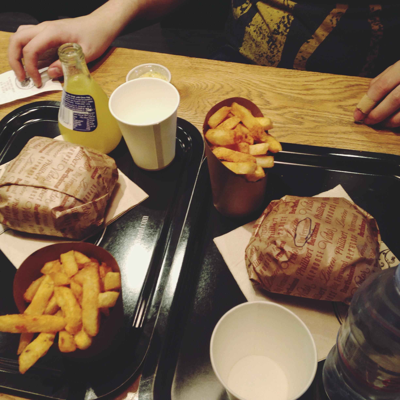 Mano del consorte con hamburgé e le patatine della vita.